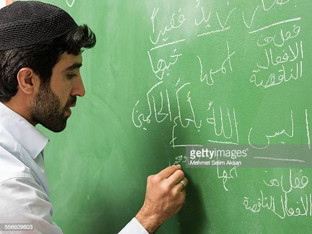 Muslim Teacher With Skullcap Writing On Blackboard