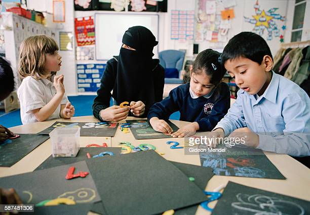 A Muslim teaching assistant works with Reception pupils at Millfields Community School A large number of Muslim children attend the school a large...