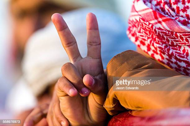 A Muslim teenager gives the Peace sign with his fingers during a camel race in the desert.