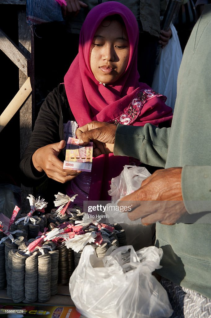MARKET, KINTAMANI, BALI, INDONESIA - : A muslim vendor from Madura sells chinese coins used in Balinese Hindu rituals to Balinese in the Kintamani market. Long know for their aggressive business sense, Madurese can be found in nearly every traditional retail market in Bali..