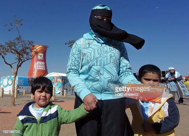 A Muslim woman and her children arrive holding tickets outside Soccer City stadium ahead of the Group B first round 2010 World Cup football match...