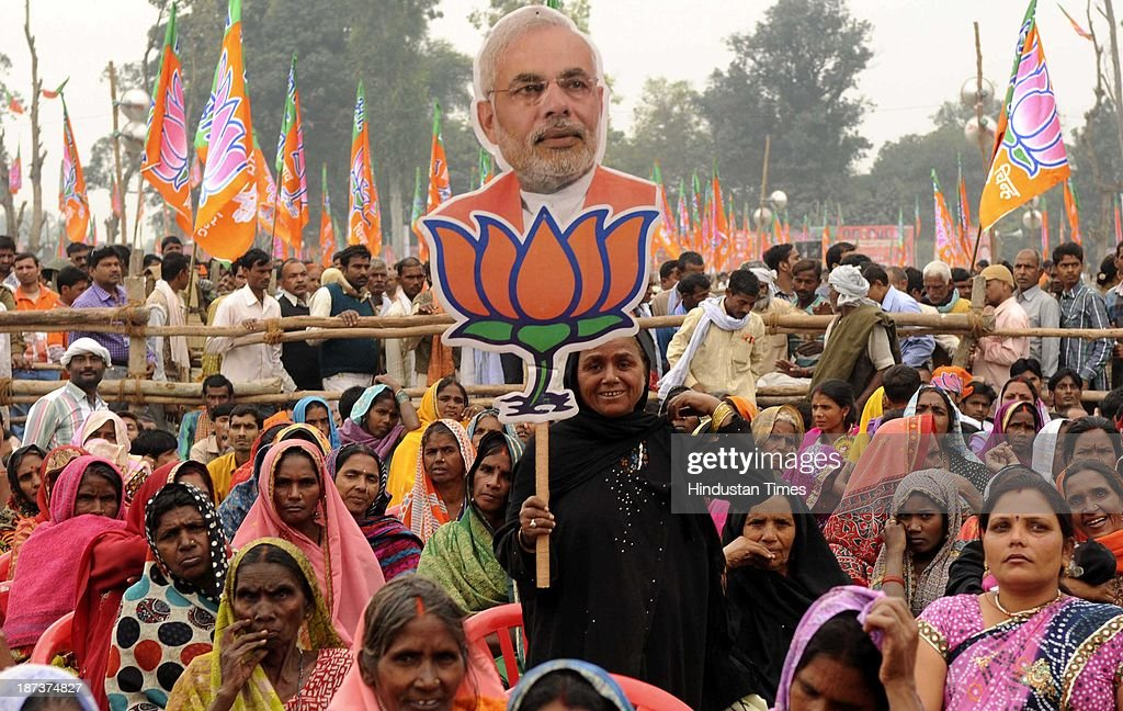A Muslim woman BJP supporter with cutout of BJP prime ministerial candidate Narendra Modi during his rally at Begumpur Sohrawa village on November 8, 2013 in Bahraich, India. In a hard-hitting attack on the Congress, Bahujan Samaj Party and Samajwadi Party at a rally here, Modi said the three parties had similar DNA, and urged people of Uttar Pradesh to give a decisive mandate to the BJP in the 2014 Lok Sabha polls.