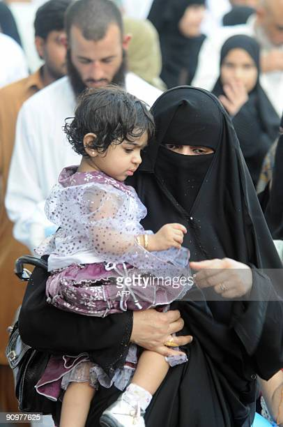 A Muslim woman carries her daughter after performing the early morning Eid alFitr prayer in the Saudi holy city of Mecca on September 20 2009 Most...