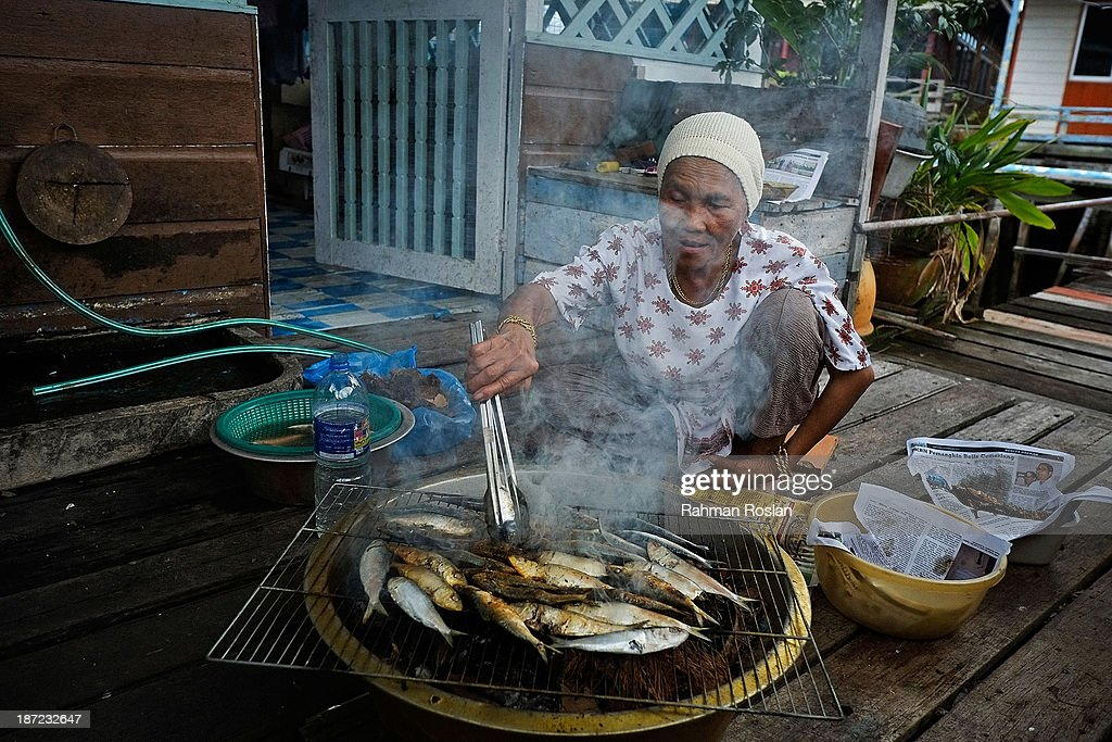 A muslim woman cooks fresh fish as she prepares lunch for her family at Kampung Air on November 7, 2013 in Bandar Seri Begawan, Brunei Darussalam. Sultan Hassanal Bolkiah has announced the introduction of a new Sharia penal code to be applied only to Muslims in the East Asian country. The Sultan of Brunei said the phasing in of the new code would begin in six months with reports that punishments could include stoning for offences such as adultery.