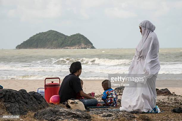 Muslim woman dressed in white stands on a beach with her family along the South China Sea
