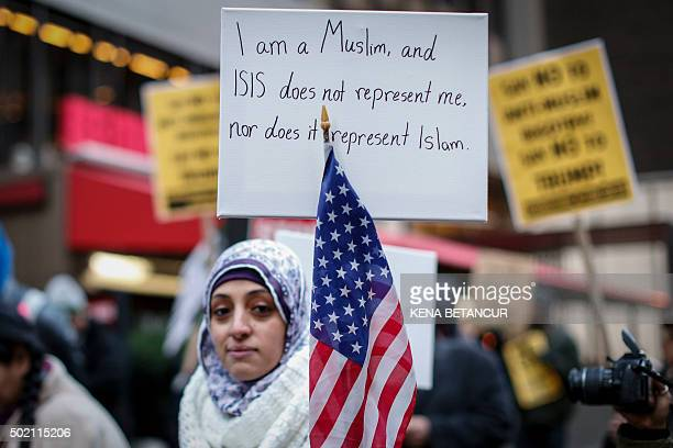A Muslim woman holds a poster during a protest against Donald Trump on December 20 2015 in New York Republican presidential hopeful Donald Trump...