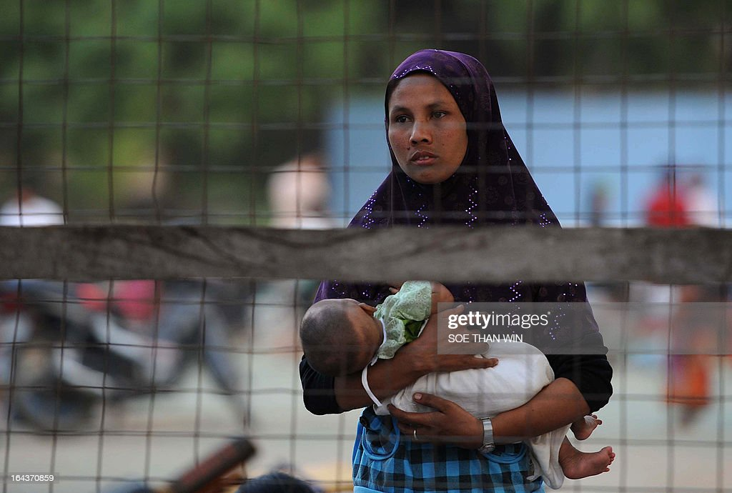 A Muslim woman holds her baby as she looks out from a temporary relief camp in riot-hit Meiktila on March 23, 2013. Troops patrolled the streets of a central Myanmar town on March 23 after Buddhist-Muslim unrest tore through the area leaving at least 20 dead and spurring the government to declare emergency rule. AFP PHOTO/ Soe Than WIN