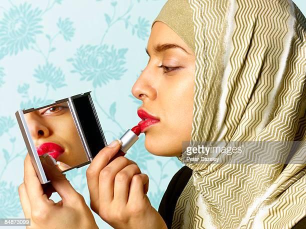Muslim Woman in Hi-Jab applying lipstick.