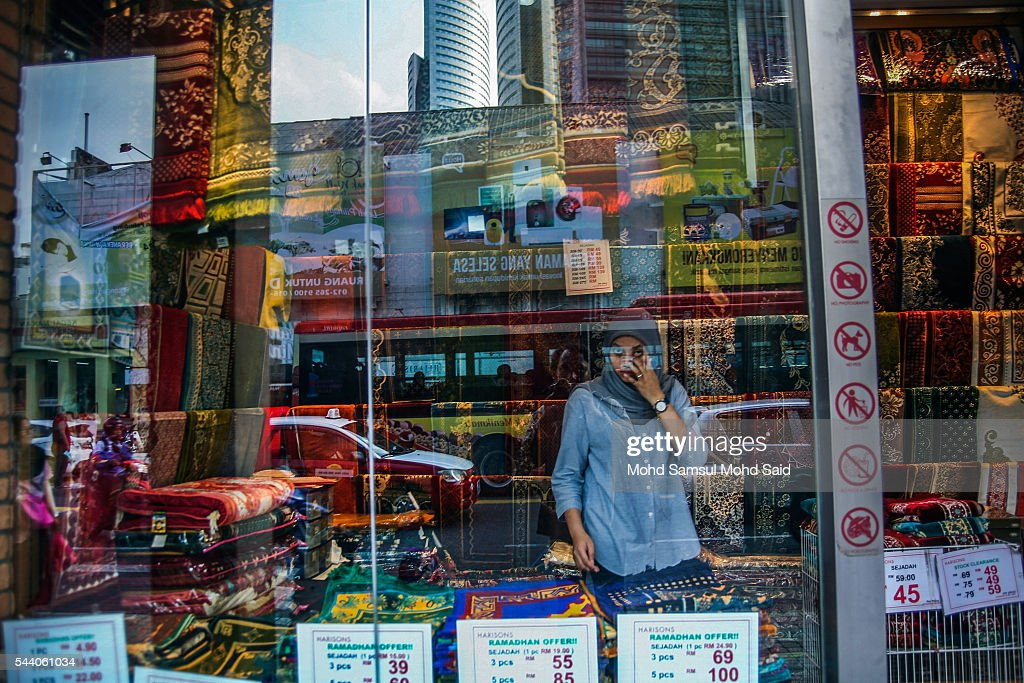 A Muslim woman is seen inside the shop in downtown ahead of the Eid al-Fitri festival on July 1, 2016 in Kuala Lumpur, Malaysia. Southeast Asia's Muslims are observing the fasting month of Ramadan, Islam's holiest month, during which observant believers fast from dawn to dusk. Malaysia Muslims spend extra on food and new clothes for Eid al-Fitr, the most important festival in Islam, which marks the end of Ramadan spending seems to be holding up in Malaysia and in neighbouring Indonesia, which together account for about 14 percent of the world's Muslims.