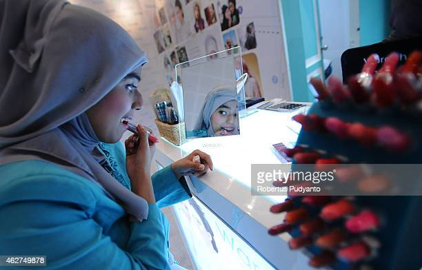 Muslim woman puts lipstick during Indonesia Moslem Fashion Expo on February 4 2015 in Surabaya Indonesia Indonesia hopes to become the 'Paris of...