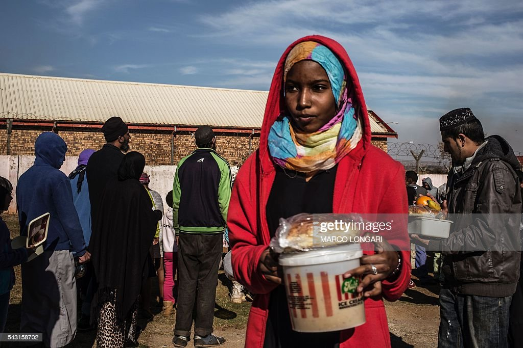 A Muslim woman receives food before breaking the fast for Ramadan in Lenasia, on the outskirts of Johannesburg, on June 26, 2016. Muslims throughout the world are marking the month of Ramadan, the holiest month in the Islamic calendar, during which devotees fast from dawn until dusk. / AFP / MARCO