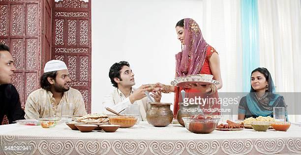 Muslim woman serving food during Id