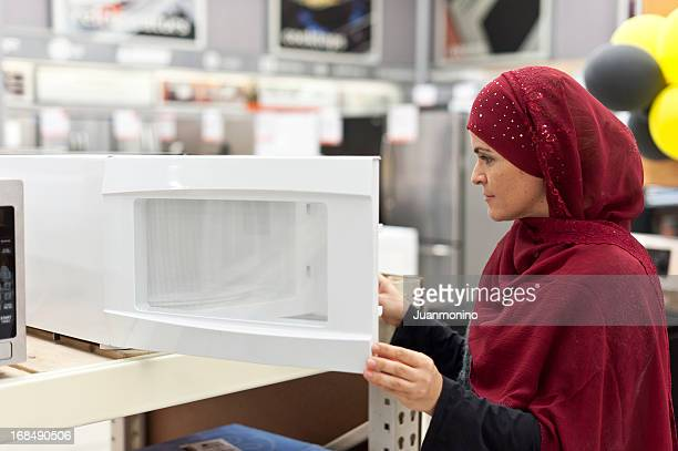 Muslim woman shopping for a microwave oven