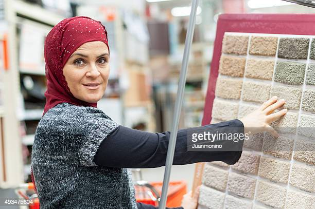 Muslim woman shopping for carpet