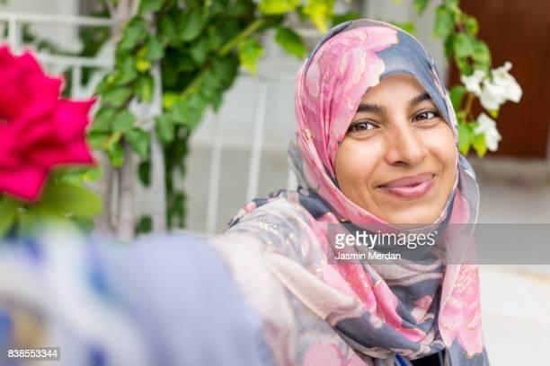 Muslim woman sitting in backyard making selfie with phone