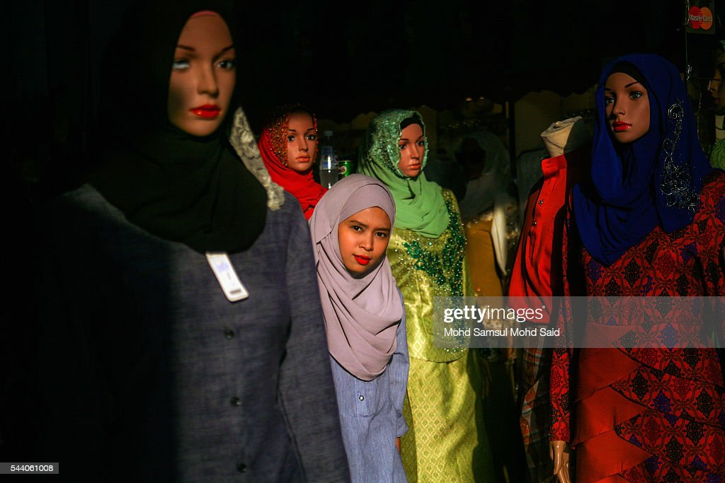 Muslim woman smile near the mannequin after shops for her clothes ahead of the Eid al-Fitri festival on July 1, 2016 in Kuala Lumpur, Malaysia. Southeast Asia's Muslims are observing the fasting month of Ramadan, Islam's holiest month, during which observant believers fast from dawn to dusk. Malaysia Muslims spend extra on food and new clothes for Eid al-Fitr, the most important festival in Islam, which marks the end of Ramadan spending seems to be holding up in Malaysia and in neighbouring Indonesia, which together account for about 14 percent of the world's Muslims.