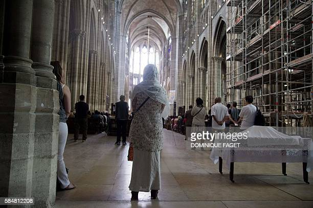 A Muslim woman stands as she attends a Mass in tribute to priest Jacques Hamel in the SaintDenis Cathedral on July 31 2016 Muslims across France were...