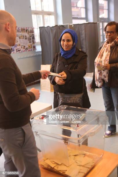 Muslim woman votes in the first round of the Presidential race in the Belleville neighbourhood a mixed ethnic area in the 19th arrondissement on...