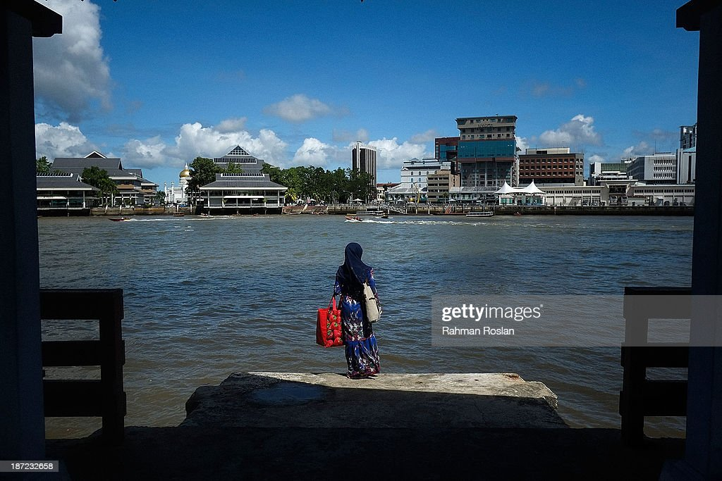 A muslim woman waits for a boat to pick her up from a jetty at Kampung Air on November 7, 2013 in Bandar Seri Begawan, Brunei Darussalam. Sultan Hassanal Bolkiah has announced the introduction of a new Sharia penal code to be applied only to Muslims in the East Asian country. The Sultan of Brunei said the phasing in of the new code would begin in six months with reports that punishments could include stoning for offences such as adultery.