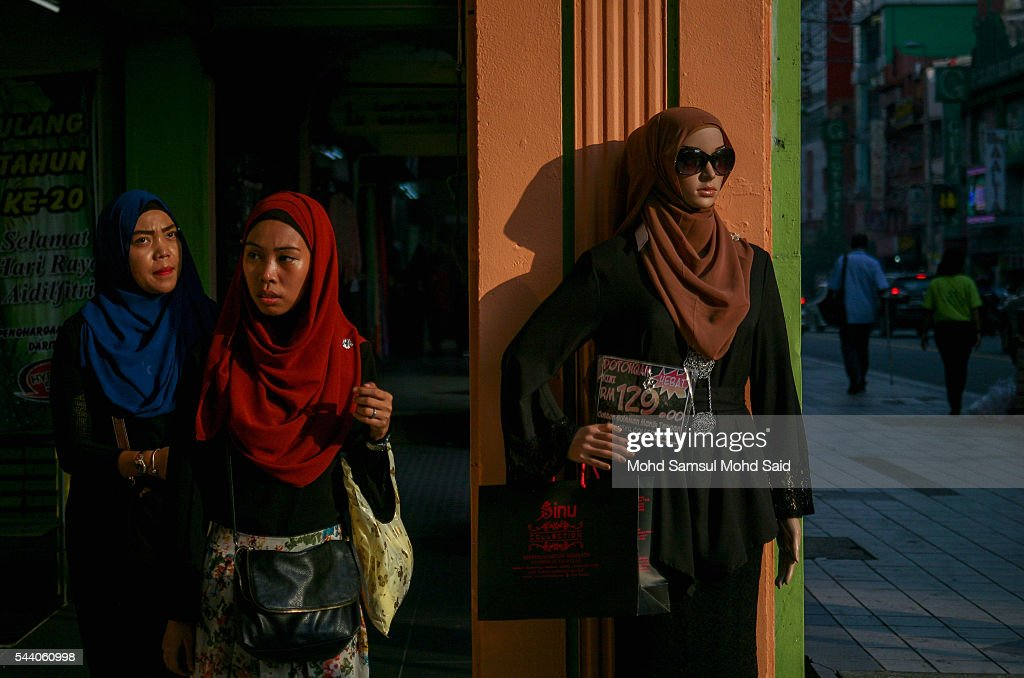 A Muslim woman walk past the mannequin after shops for clothes ahead of the Eid al-Fitri festival on July 1, 2016 in Kuala Lumpur, Malaysia. Southeast Asia's Muslims are observing the fasting month of Ramadan, Islam's holiest month, during which observant believers fast from dawn to dusk. Malaysia Muslims spend extra on food and new clothes for Eid al-Fitr, the most important festival in Islam, which marks the end of Ramadan spending seems to be holding up in Malaysia and in neighbouring Indonesia, which together account for about 14 percent of the world's Muslims.