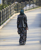 Muslim woman walking along the road in the park
