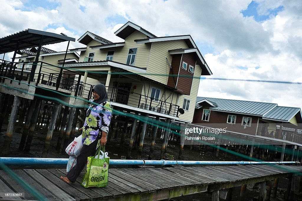 A muslim woman walks past a newly built government house at Kampung Air on November 7, 2013 in Bandar Seri Begawan, Brunei Darussalam. Sultan Hassanal Bolkiah has announced the introduction of a new Sharia penal code to be applied only to Muslims in the East Asian country. The Sultan of Brunei said the phasing in of the new code would begin in six months with reports that punishments could include stoning for offences such as adultery.