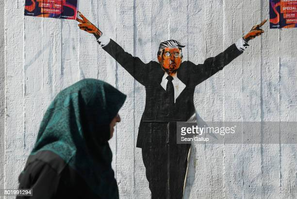Muslim woman walks past a street artist's rendition of US President Donald Trump on June 27 2017 in Berlin Germany The US Supreme Court recently...