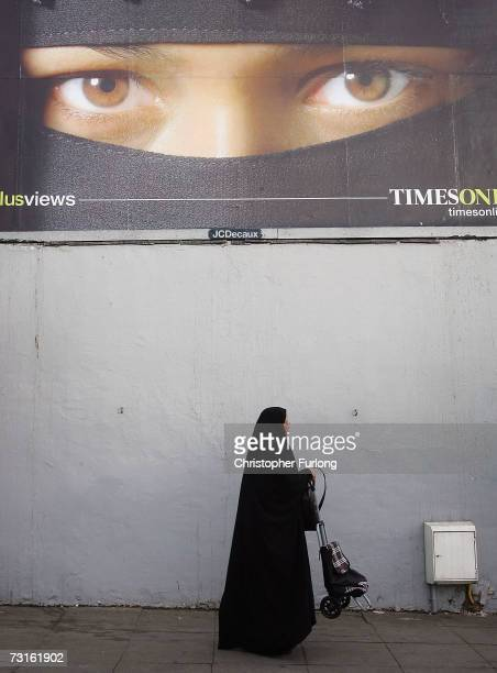 Muslim woman walks past an advertising billboard in the Bordesley Green area of Birmingham near to the location of a series of antiterror dawn raids...