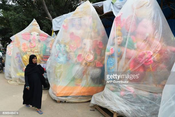 Muslim woman walks past clay idols of the Hindu elephant God Ganesh covered in polythene sheets at a road side stall ahead of the Ganesh Chaturthi...