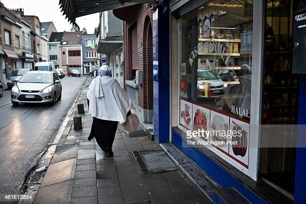 Muslim woman walks past halal shops on January 13 2014 in Vilvoorde Belgium