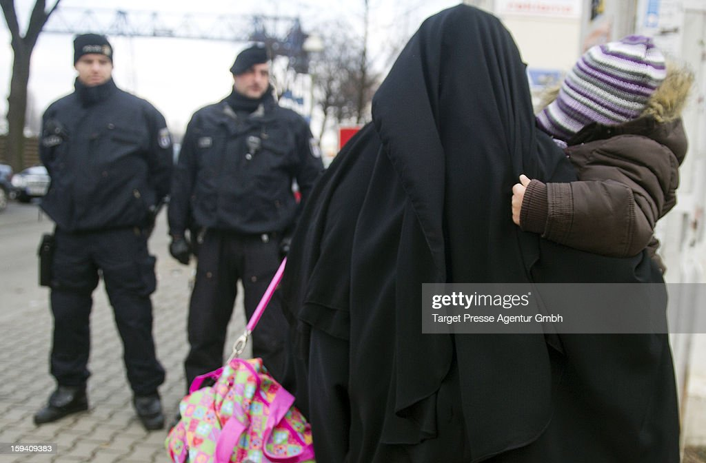 A Muslim woman, wearing a burqa, carries a child as she walks past police outside a building where Salafites are holding a benefit rally for Syrian Muslims on January 13, 2013 in Berlin. Two dozen members of 'Pro Deutschland' waited in the centre of Berlin for Salafites who originally planned to hold a public gathering to raise money for Muslims in Syria, which included prominent speakers such as radical Islamic preacher Pierre Vogel. They then moved the event to a private gathering in Neukoelln district. Salafites are an ultra-conservative group of Muslim sunnis with hundreds of members in Berlin and the area around Bonn and cologne. German authorities are keeping a close eye on the group, espacially since clashes that broke out last year in which Salafite demonstrators attacked police and right-wing counter-demonstrators. on January 13, 2013 in Berlin, Germany.