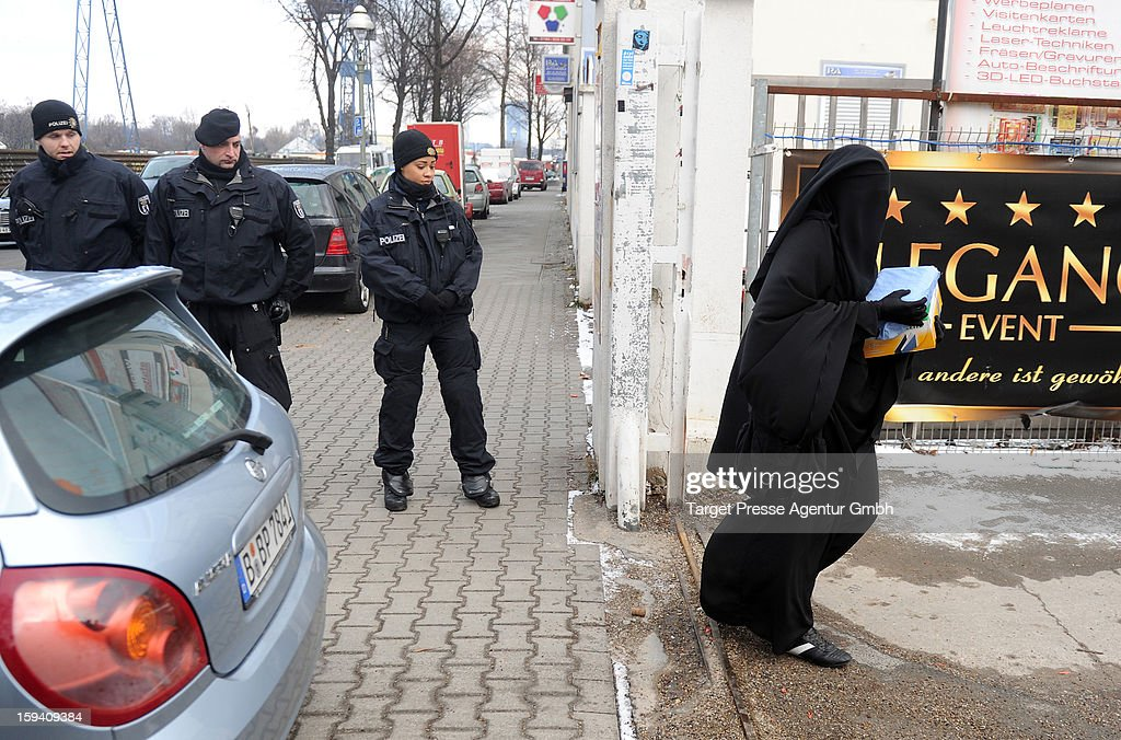 A Muslim woman wearing a burqa walks past police outside a building where Salafites are holding a benefit rally for Syrian Muslims on January 13, 2013 in Berlin. Two dozen members of 'Pro Deutschland' waited in the centre of Berlin for Salafites who originally planned to hold a public gathering to raise money for Muslims in Syria, which included prominent speakers such as radical Islamic preacher Pierre Vogel. They then moved the event to a private gathering in Neukoelln district. Salafites are an ultra-conservative group of Muslim sunnis with hundreds of members in Berlin and the area around Bonn and cologne. German authorities are keeping a close eye on the group, espacially since clashes that broke out last year in which Salafite demonstrators attacked police and right-wing counter-demonstrators. on January 13, 2013 in Berlin, Germany.