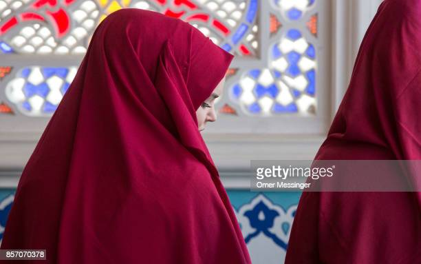 Muslim woman wearing a 'Chador' head cover is seen during midday prayers at Sehitlik mosque which is mostly Turkish on Open Mosque Day on October 3...