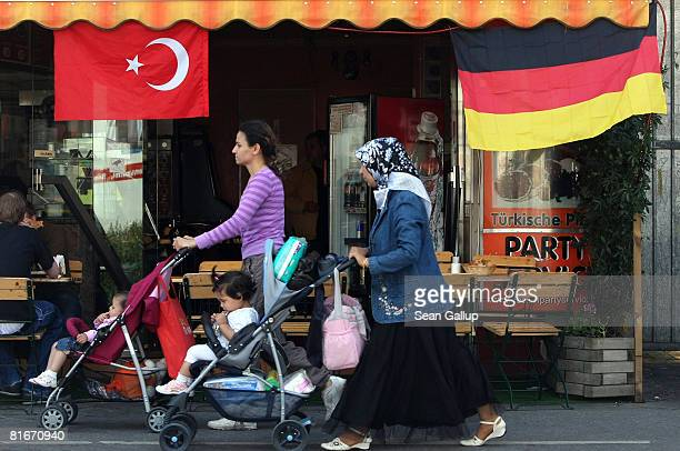 Muslim woman wearing a headscarf pushes a pram past German and Turkish flags fluttering from the awning of a cafe in the immigrantheavy district of...