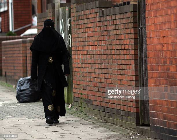 A muslim woman wearing a traditional burqa walks through the streets of Birmingham's Spark Hill area on January 27 2010 in Birmingham United Kingdom...