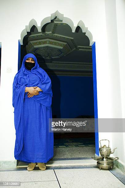 Muslim woman wearing the traditional chador or nikab (full body cloak) standing under the curved archway entrance of house, Morocco. (MR)