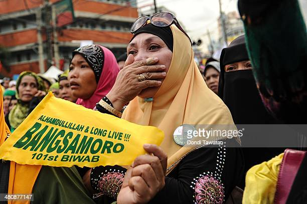 Muslim woman wipes her tears after the conclusion of the signing of the Comprehensive Agreement on the Bangsamoro between the Philippine government...