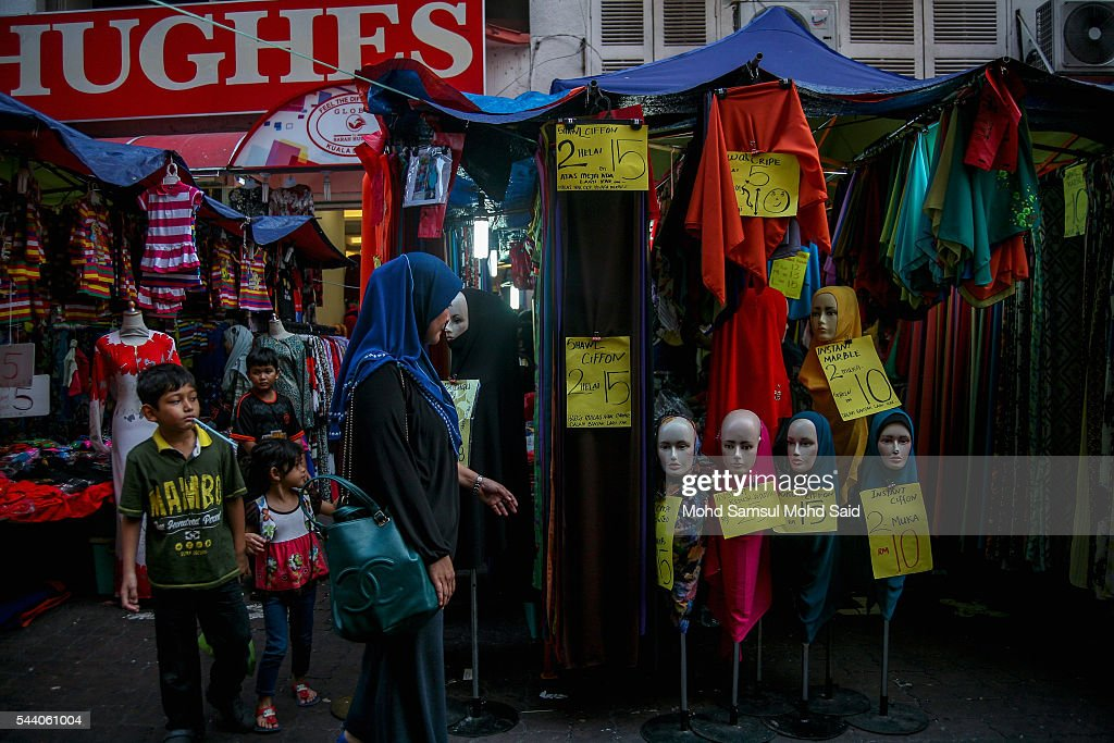A Muslim woman with her chldren shops for their clothes ahead of the Eid al-Fitri festival on July 1, 2016 in Kuala Lumpur, Malaysia. Southeast Asia's Muslims are observing the fasting month of Ramadan, Islam's holiest month, during which observant believers fast from dawn to dusk. Malaysia Muslims spend extra on food and new clothes for Eid al-Fitr, the most important festival in Islam, which marks the end of Ramadan spending seems to be holding up in Malaysia and in neighbouring Indonesia, which together account for about 14 percent of the world's Muslims.