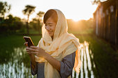 asian young muslim woman with smartphone outdoor in sunset