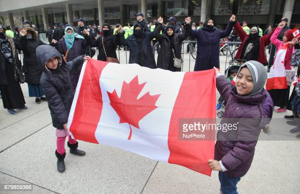 Muslim women and children form a 'circle of peace' during a rally against Islamophobia White Supremacy amp Fascism in downtown Toronto Ontario Canada...