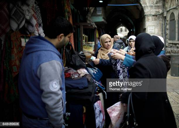 Muslim women at a market stall with clothes street scene in the Muslim quarter in the historic city center of Jerusalem on February 08 2017 in...