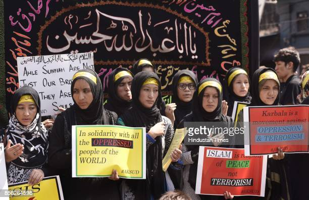 Muslim women devotees holding placard against ISIS on Islam take part in a mourning procession marking the day of Ashura 10 MuharramulHaram at Shia...
