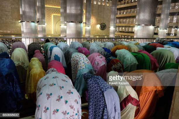 Muslim women dressed in colorful dresses and veils seen during Friday Prayer ceremony on a balcony allocated for females in Istiqlal Mosque on...