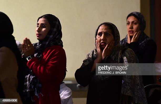 Muslim women gesture in prayer while congregating outside the Baitul Hameed Mosque at the Ahmadiyya Muslim Community in Chino California on December...