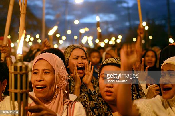 Muslim women hold torches during a peace vigil in the Muslim community of Maharlika Village on March 6 2013 in Taguig Philippines The peace rally was...