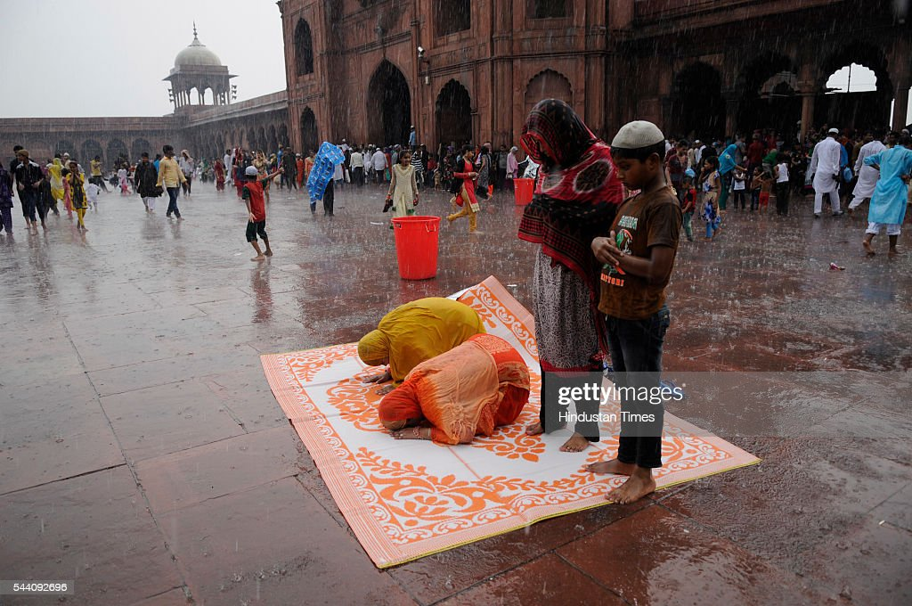 Muslim women offering prayer as it rains heavily near Jama Masjid on July 1, 2016 in New Delhi, India. The capital received its first Monsoon rains dragging the maximum temperatures several notches below normal. Heavy downpour caused water logging and traffic jams in the city.