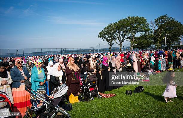 Muslim women pray during the traditional outdoor EidalFitr celebrations July 17 2015 in the Brooklyn borough of New York The Eid holiday marks the...