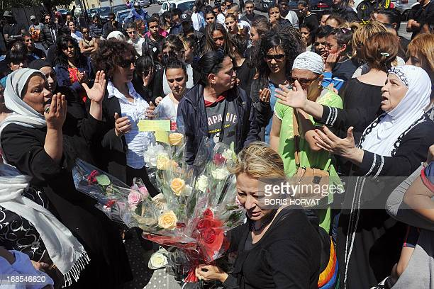 Muslim women pray while around one hundred friends and relatives mourn on May 11 2013 at the site where a 17yearold has been riddled with bullets in...