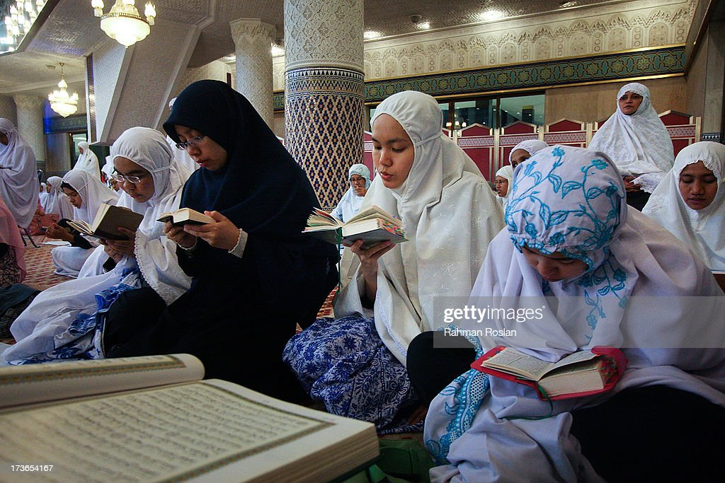 Muslim women recites The Koran while waiting for the night prayer known as Tarawikh to start as millions of Muslims observe the holiday of Ramadhan on July 16, 2013 in Kuala Lumpur, Malaysia. During Ramadhan, Muslims refrain from consuming food, drinking liquids, smoking, swearing, and engaging in sexual relations from dawn till sunset.