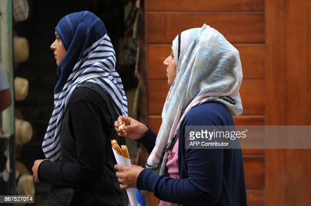 Muslim women walk along a street of Havana on October 27 2017 Almost drowned by the crisis of the 90s the emerging Cuban fashion begins to thrive...